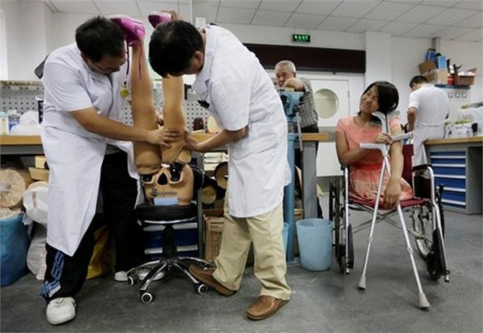 Hongyan vui vẻ ngồi nhìn các bác sĩ chỉnh sửa đôi chân giả của mình.