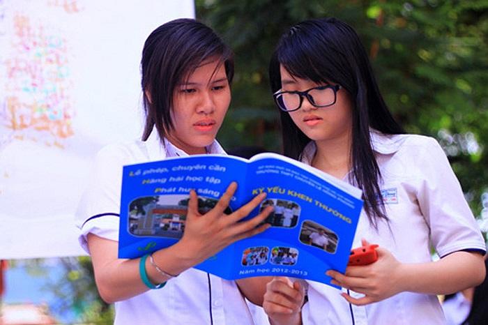 Hai nữ sinh xem kỷ yếu của trường.