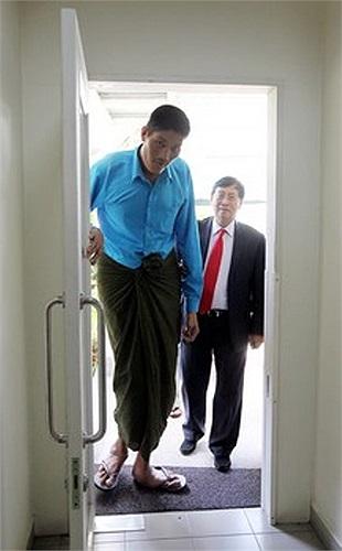 Hình ảnh người đàn ông cao kều bước vào một chiếc cửa cao hơn 2,3 mét. Theo sau anh là một chuyên viên y tế.