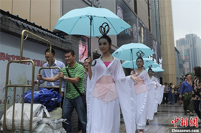 Những cô gái mặc trang phục trắng, cầm ô xanh đi dạo trên phố thu hút sự chú ý của người qua đường