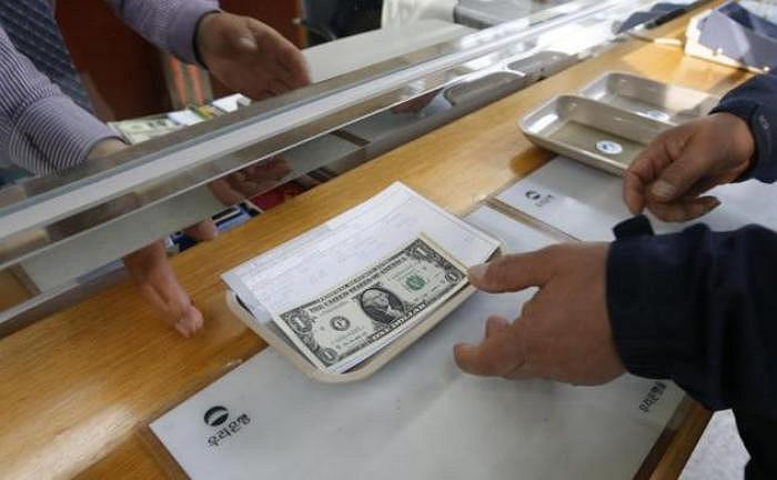 Một doanh nhân người Hàn Quốc đang đổi tiền USD tại một chi nhánh ngân hàng nằm trong khu vực hải quan của Hàn Quốc trước khi vào khu công nghiệp Kaesong trên đất Triều Tiên (Ảnh chụp hôm 1/4/2013)