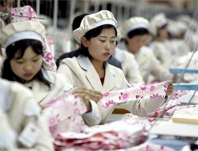 Các công nhân Triều Tiên đang làm việc tại một nhà máy sản xuất hàng may mặc của công ty Shinwon trong khu công nghiệp liên Triều Kaesong nằm cách khu phi quân sự chưa đến 100km (Ảnh chụp năm 2005)