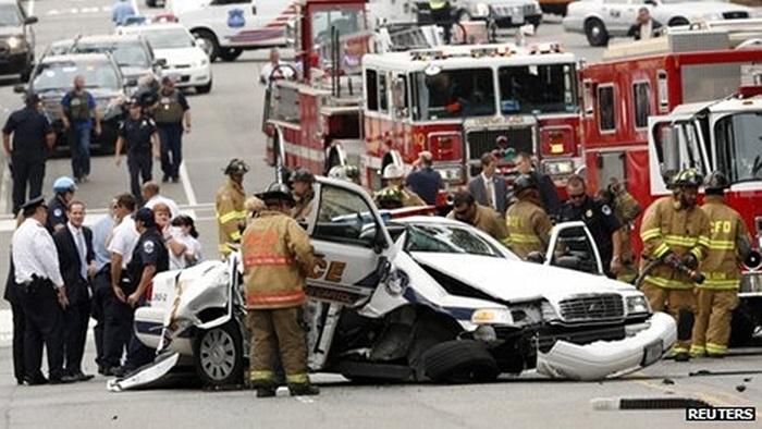 Nhân viên cứu hộ bên cạnh chiếc xe cảnh sát bị hư hại sau vụ rượt đuổi