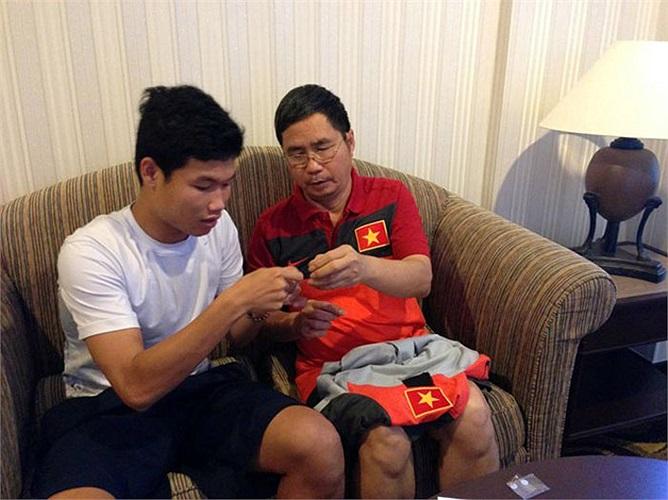 Trưởng đoàn U19 Việt Nam, ông Dương Nghiệp Khôi cùng tiền vệ Đông Triều chuẩn bị băng đen khâu lên ngực áo của các cầu thủ