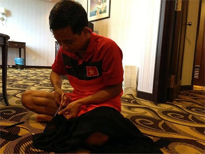 Bác sĩ Dương Hoàng Nghĩa cẩn thận cắt miếng vải lớn thành các băng tang nhỏ