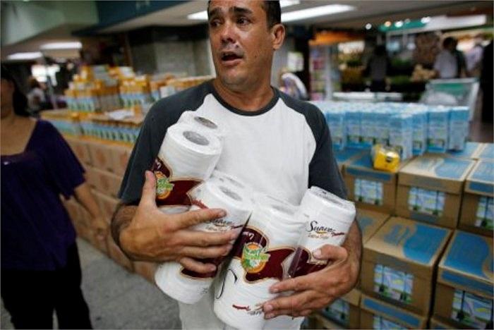 Một người đàn ông ôm trong tay nhiều cuộn giấy vệ sinh. Có khách hàng đã phải đi tìm mua giấy vệ sinh trong 2 tuần mới mua được tại thủ đô Caracas