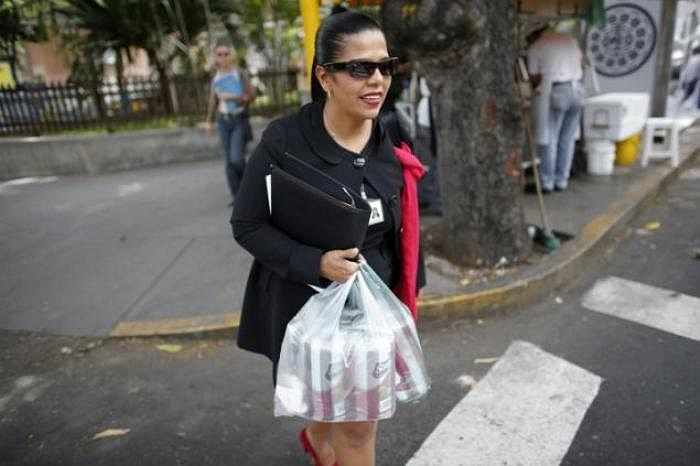 Một phụ nữ tươi cười vì đã mua được một ít giấy vệ sinh mang về nhà