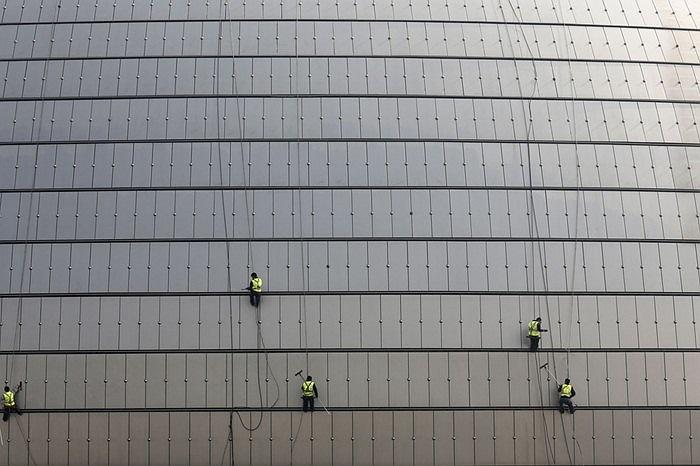 Công nhân làm vệ sinh các ô cửa kính tại Nhà hát quốc gia ở Bắc Kinh, Trung Quốc