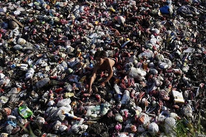 Cậu bé nhặt những đồ nhựa có thể tái chế trong dòng nước thải ở Lahore, Pakistan