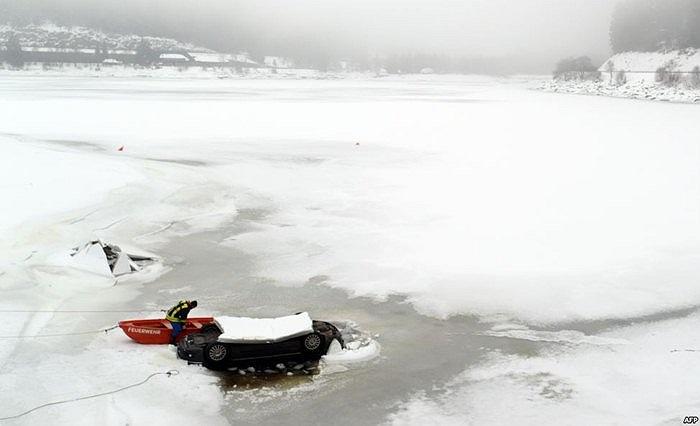 Lính cứu hỏa đang cố gắng cứu hộ chiếc xe bị kẹt trong băng ở Đức