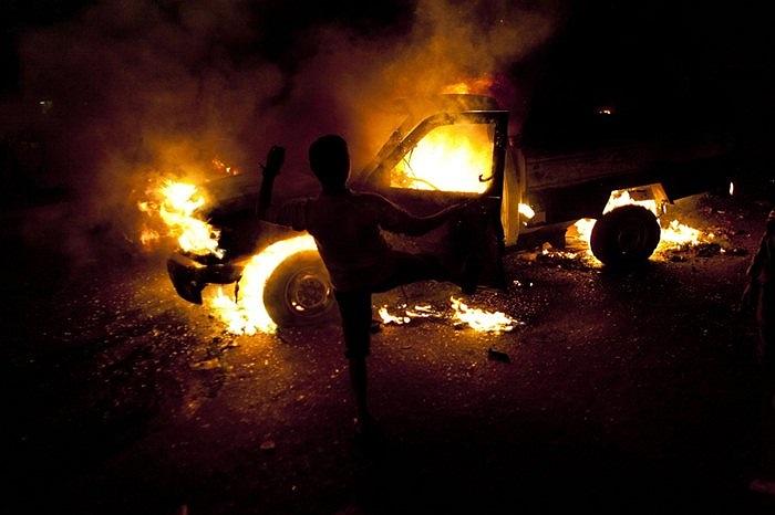 Người biểu tình đang sút vào chiếc xe cảnh sát bốc cháy tại Cairo, Ai Cập