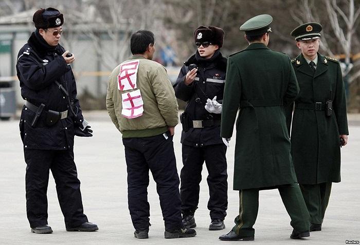 Một người đàn ông mặc chiếc áo in chữ: Dân Chủ bị cảnh sát hỏi thăm trước quảng trường Thiên An Môn, Bắc Kinh, Trung Quốc