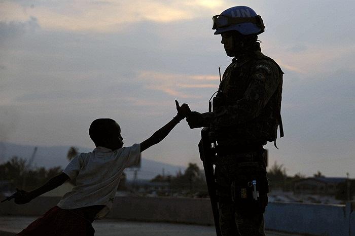 Lính gìn giữ hòa bình Liên Hiệp Quốc ở Haiti bắt tay cùng cậu bé địa phương
