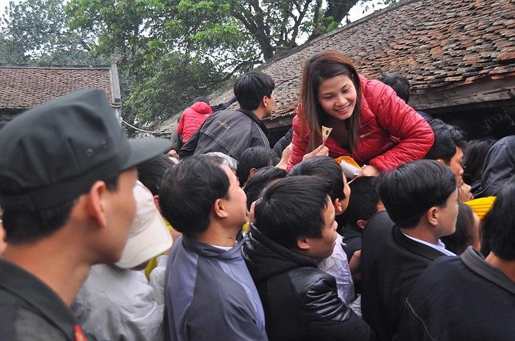 Phụ nữ cũng không kém cạnh khi luồn lách giữa đám đông để xin ấn