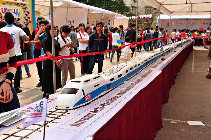 Chiếc bánh ga tô hình đoàn tàu dài 20m đạt kỉ lục Việt Nam là điểm nhấn thú vị thu hút sự chú ý của các sinh viên và khách mời đến tham dự Ngày hội văn hóa tôn vinh Cộng đồng Pháp ngữ