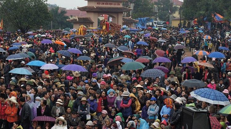 Rất đông người dân ngồi dưới mưa nghe hát quan họ