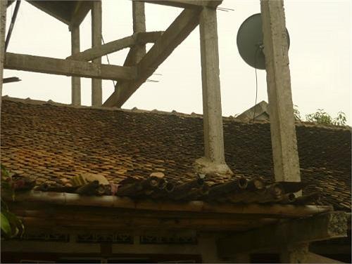 Một bên là những cây cột xi măng đổ xuyên qua ngôi nhà cấp 4