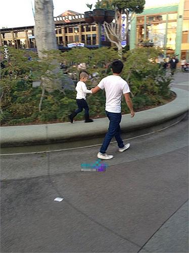 Cậu nhóc được bố dắt đi dạo.