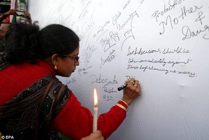 Một phụ nữ tới ký tên trên bảng phản đối nạn cưỡng hiếp ở nước này