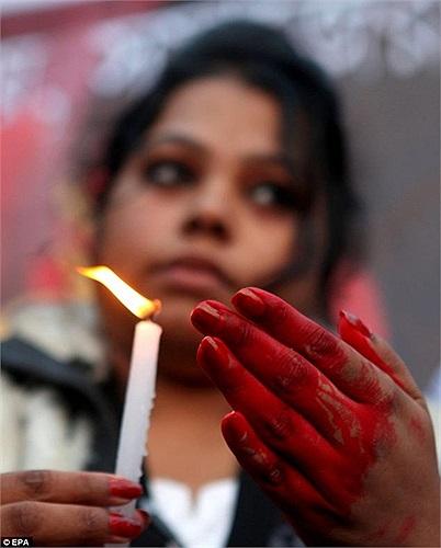 Một phụ nữ cầm nến cầu nguyện cho nạn nhân