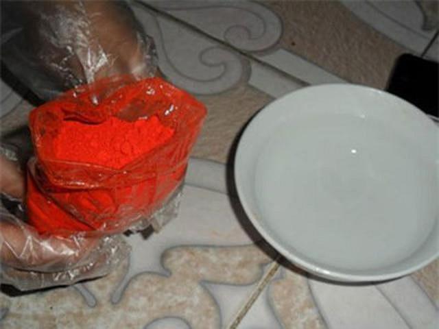 Sau đó cho một ít bột phẩm màu hoa hiên vào bát nước và hòa tan.
