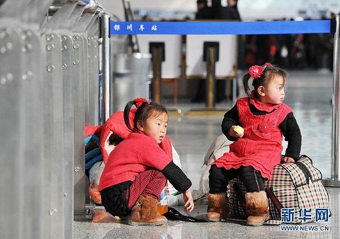 Những em nhỏ ngồi chờ bố mẹ làm thủ tục ở nhà ga