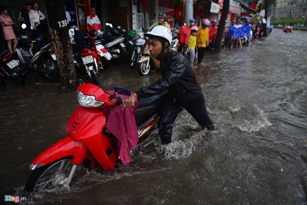 Nhiều xe chết máy phải dắt bộ trên đoạn đường ngập nước .