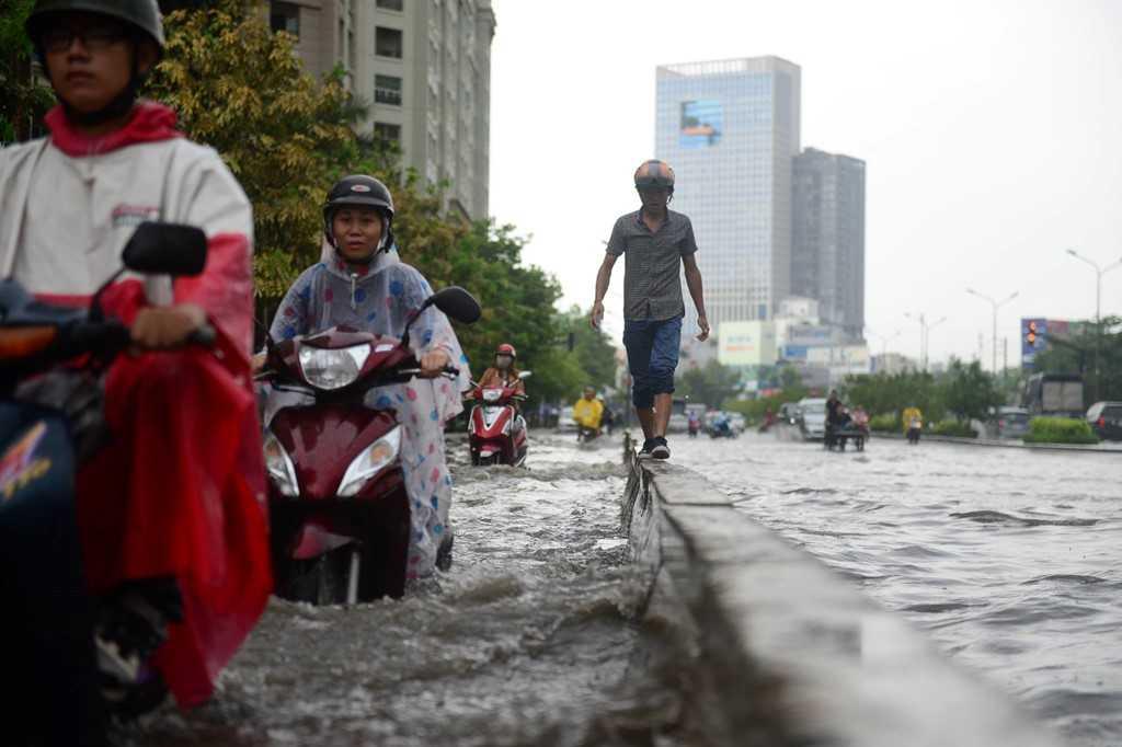 Để tránh nước ngập một thanh niên phải đi bộ trên con lươn phân cách làn xe .