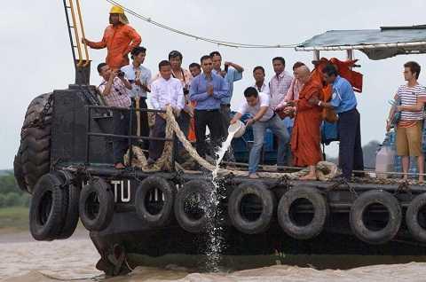 Một nhà sư đang làm lễ trước khi các thợ lặn tiến hành tìm kiếm Đại Chung trên sông Yangon.
