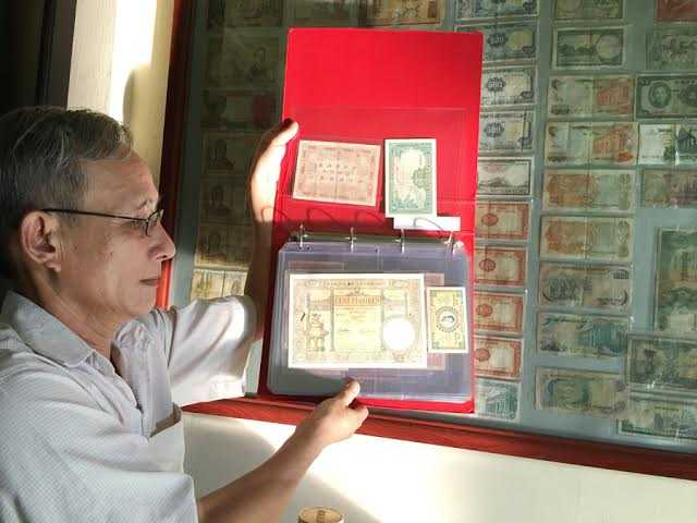 Thầy Thành với một trong số tiền giấy đã sưu tập được