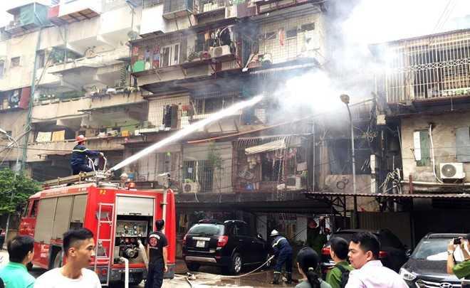 Cảnh sát dùng vòi rồng khống chế ngọn lửa ở căn hộ tầng 3 khu tập thể. Ảnh: Minh Quân.