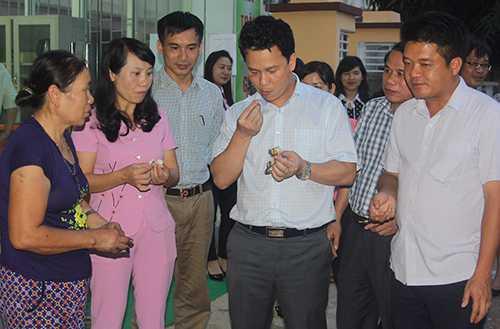 Ông Đặng Quốc Khánh (thứ 4 từ trái qua) thưởng thức cá nướng với tiểu thương tại cửa hàng kinh doanh ở đường Võ Liêm Sơn (TP Hà Tĩnh). Ảnh: D.T
