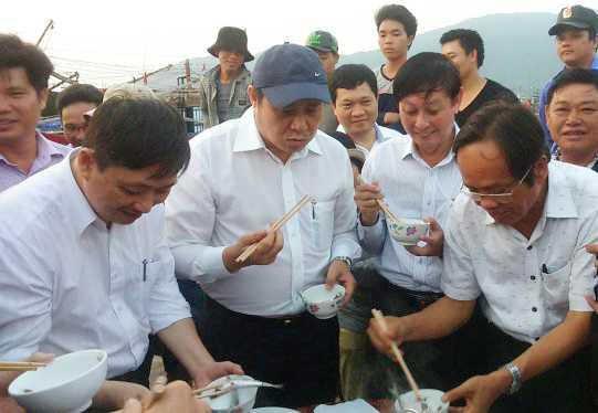 Chủ tịch UBND TP Đà Nẵng (đội mũ) ăn cá tại cảng cá Thọ Quang để dân an tâm - Ảnh: Đoàn Cường