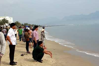 Người dân hiếu kỳ xem cá heo dạt vào bờ.