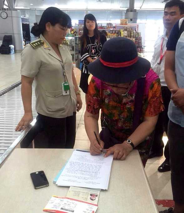 Bà Yan Fengge ký vào biên bản của lực lượng chức năng tại sân bay Cam Ranh, thừa nhận đã trộm điện thoại di động của đồng hương đi cùng chuyến bay - Ảnh: An ninh sân bay Cam Ranh cung cấp
