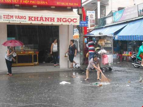 Người dân ở gần khu chợ quét rác để ngăn rác tràn vào nhà. ẢNH: THANH TUYỀN