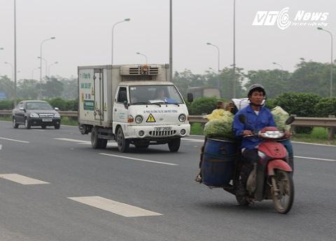 Xe máy chở hàng chen lấn với xe trọng tải rất nguy hiểm