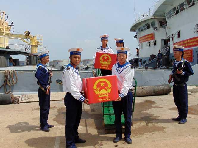Hai thùng phiếu của hai tàu 624 và 636 được chuyển lên bờ - Ảnh: ĐÔNG HÀ