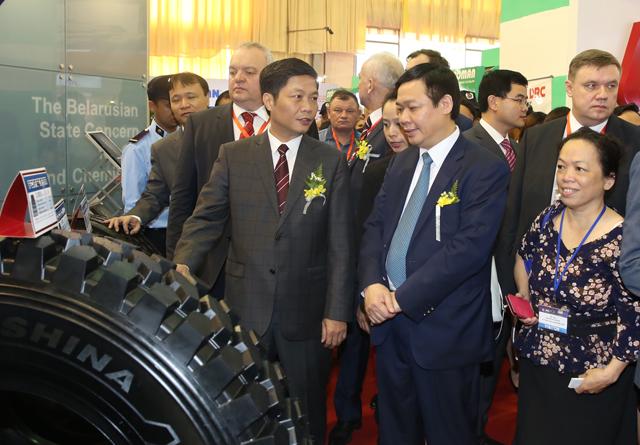 Phó Thủ tướng Vương Đình Huệ thăm gian hàng lốp <a href='http://vtc.vn/oto-xe-may.31.0.html' >ô tô</a> của Belarus, một sản phẩm xuất khẩu chủ lực của quốc gia này sang Việt Nam. Ảnh: VGP/Thành Chung