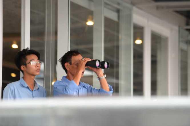 Người dân lên nhà cao tầng quan sát chiếc máy bay US Air Force (C17) - Ảnh: Hữu Khoa