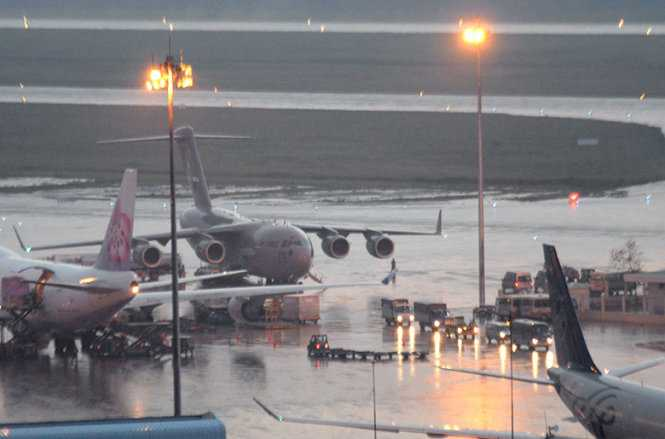 Đoàn xe chở các trang thiết bị di chuyển khỏi sân bay Tân Sơn Nhất trong cơn mưa - Ảnh: Hữu Khoa