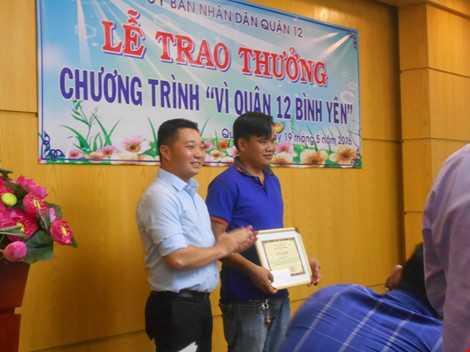 Ông Lê Trương Hải Hiếu- Chủ tịch UBND Quận 12 trao bằng khen cùng số tiền thưởng 2 triệu đồng cho anh Hồ Hiếu Tâm. ẢNH: THANH TUYỀN