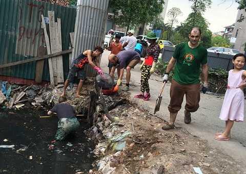 Nhóm người nước ngoài cùng các bạn học sinh, sinh viên Việt Nam đang moi rác trong cống ra.