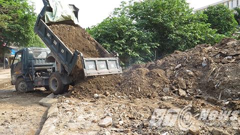 Đất cát, gạch đá chất đống như  núi bên lề đường, khi mưa chảy tràn xuống lòng đường, khi nắng bụi bay mù mịt vào nhà dân và người đi đường