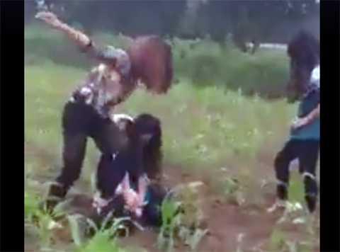 Khi nạn nhân bị ngã vật xuống ruộng ngô, người nữ đeo kính tiếp tục túm tóc, tát. Thô bạo hơn, nữ thanh niên này còn trèo lên đầu nạn nhân giẫm mấy cái
