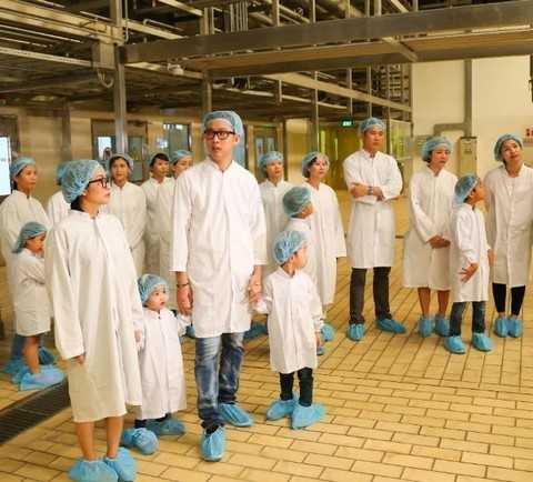 Cả gia đình trong trang phục bảo hộ ghé thăm khu vực công nghệ tiệt trùng hiện đại hàng đầu thế giới của Vinamilk.