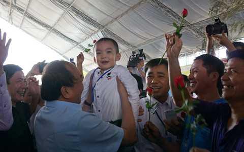 Thủ tướng Nguyễn Xuân Phúc bồng bé trai con của một công nhân - Ảnh: Hà Mi