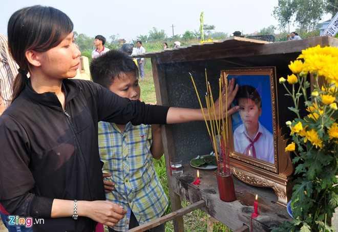 Chị Nguyễn Thị Minh Khai vuốt tay lên di ảnh trước khi giã biệt em trai Nguyễn Minh Hoàng. (Ảnh: Zing.vn).