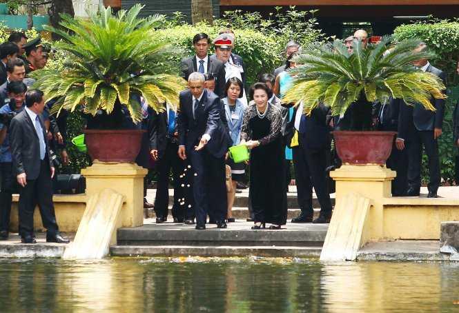 Trưa 23/5, tổng thống Mỹ đã có cuộc tiếp xúc với Chủ tịch Quốc hội Nguyễn Thị Kim Ngân. Ông được bà Kim Ngân đưa đi thăm nhà sàn Bác Hồ và cho cá ăn ở ao cá Bác Hồ (ảnh: TTO)