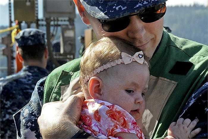 Thủy thủ John Hagenbrock ôm con gái 7 tuần tuổi của mình sau chuyến đi tuần tra trên tàu ngầm tên lửa đạn đạo USS Louisiana